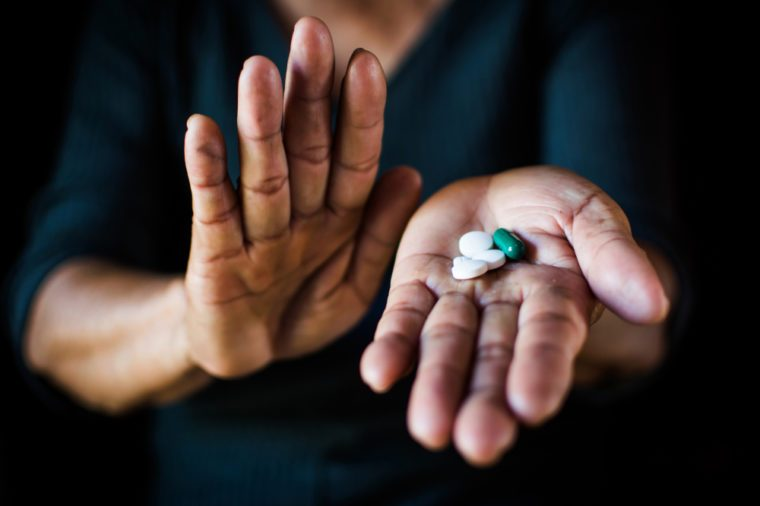 Close up hand of old woman holding a pill on black background, concept illness and healthcare