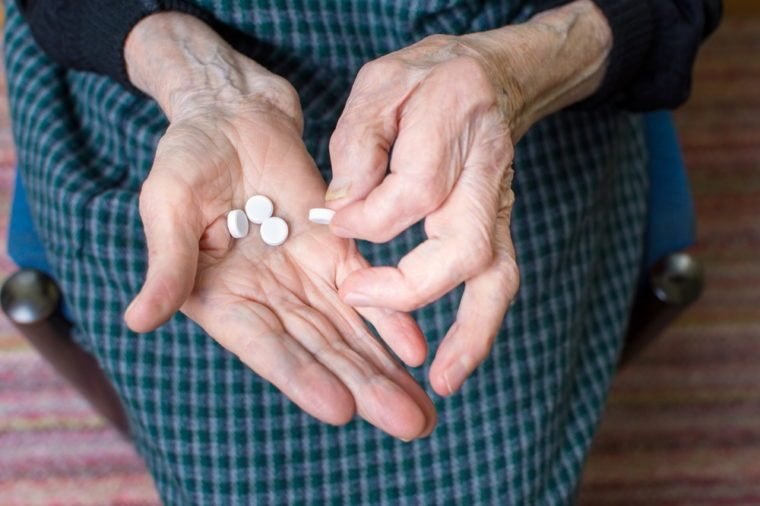 Hands of very old woman taking pills
