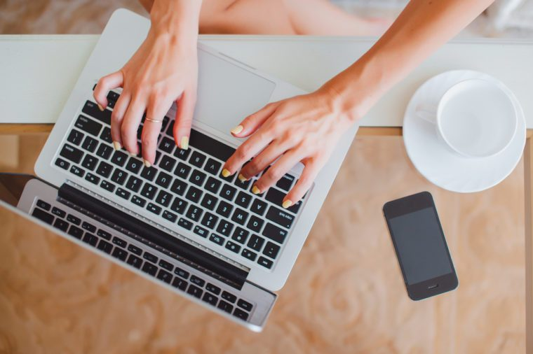 young girl woman working on a laptop sitting at home write messages to drinking coffee smiling typing on a keyboard, macbook serfing, applet style, iphone,