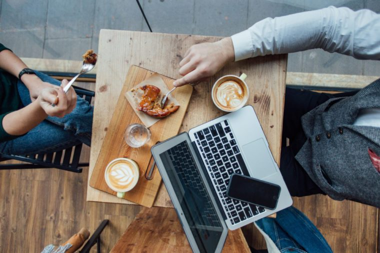 Table top photo of two friends or love couple share apple pie crumble at cafe or restaurant, drink artisan specialty coffee, talk about business or study over laptop and smartphone