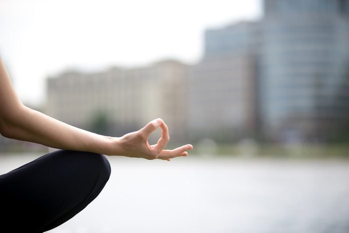 Meditation concept. Close up of hands of young office yogi woman sitting cross legged in yoga Easy Sukhasana Pose on riverbank in the city, meditating with fingers in Jnana mudra