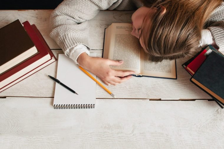 Student girl sleeping on desk with books flat lay. Top view on young tired woman napping on her textbook. Tiredness, exhaustion, education, preparing for exams concept