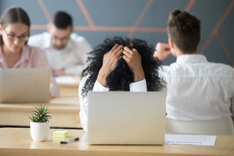 Frustrated african woman feeling despair panic shock sitting in shared office with laptop holding head in hands, upset stressed black employee or student tired of work, worried about online problem