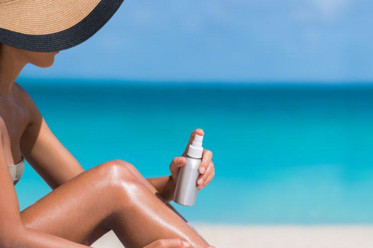 Beach body suntan skin care travel vacation. Bikini hat woman applying sunscreen lotion putting cream on tanned sexy legs sunbathing sun tanning sitting on sand with turquoise blue ocean background.
