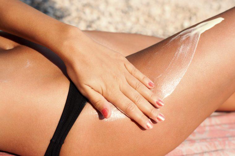 Summer holiday, applying sunscreen (suntan) creme