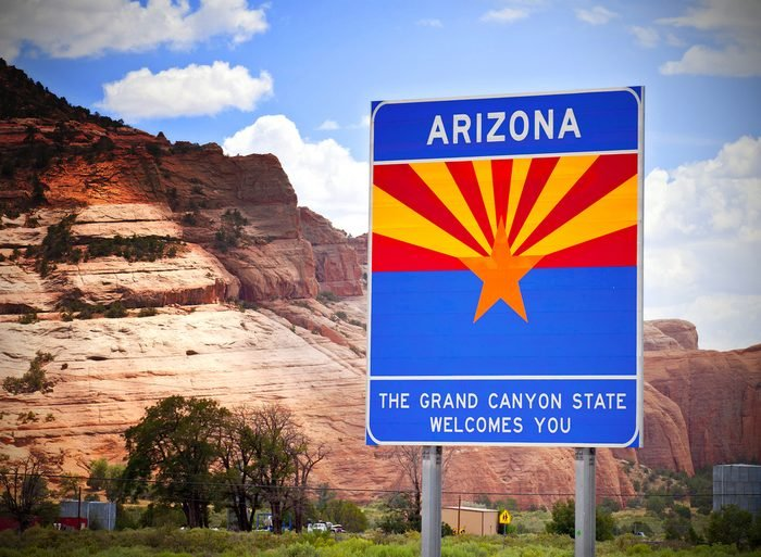 Arizona welcome sign at the state border with red rocks background