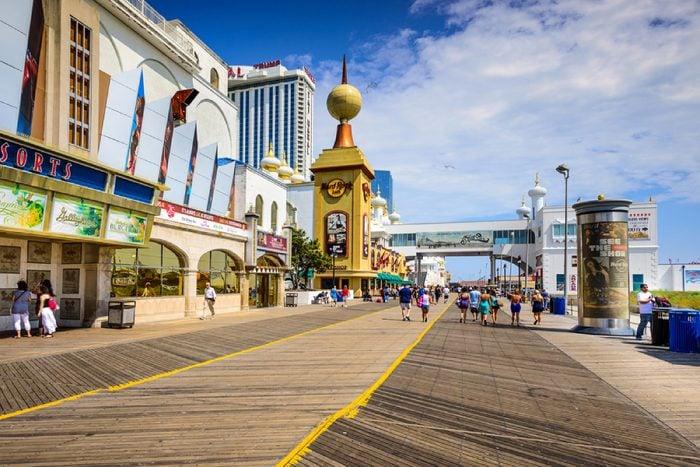 ATLANTIC CITY, NEW JERSEY - SEPTEMBER 9, 2012: Tourists walk on the boardwalk in Atlantic City.