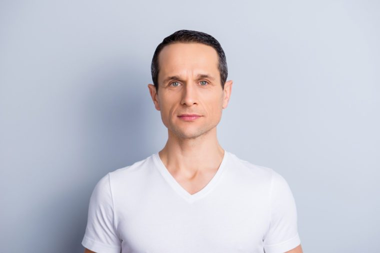 Portrait of trendy, neat, shaven, brunet man in white t-shirt with serious expression looking at camera, isolated on grey background