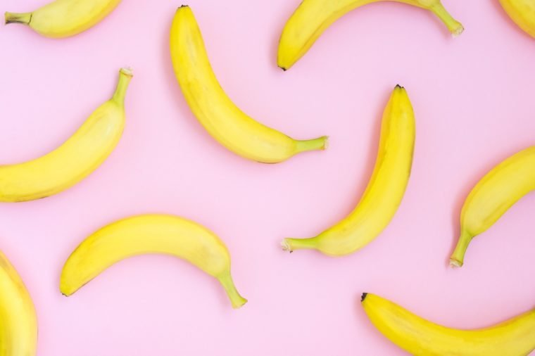 Fresh yellow bananas over pink background pattern, top view