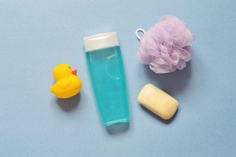 Yellow rubber duck, shampoo or shower gel, soap bar and purple sponge on a blue background. Flat lay photo baby bath products. Top view toiletries