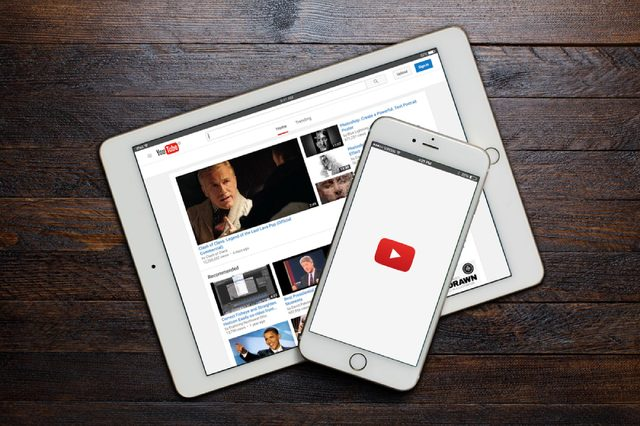 BEKASI, INDONESIA - DECEMBER 27, 2015: A loading screen of YouTube app on iPhone and a landing page of YouTube website on iPad. YouTube was founded by Chad Hurley, Steve Chen and Jawed Karim.