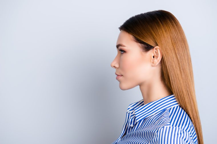 Close up cropped profile portrait of young business lady in striped shirt with serious face on pure background with copy space