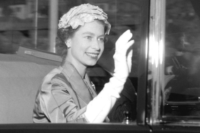Britain's Queen Elizabeth II waves to the crowd whilst travelling to a theatre in London