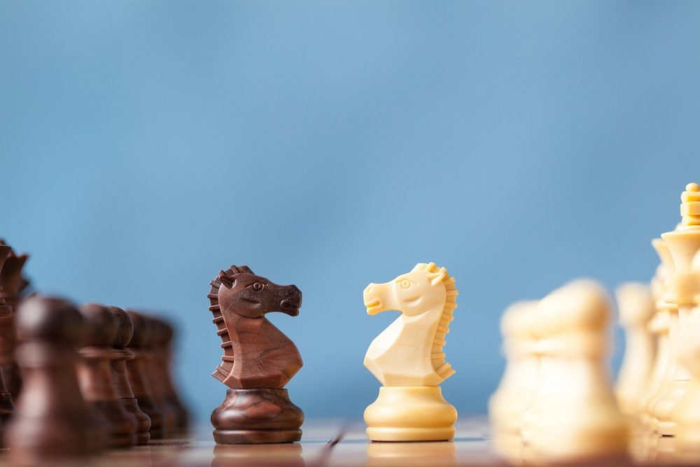 Chess pieces knights facing each other for a standoff on chessboard with blue background.