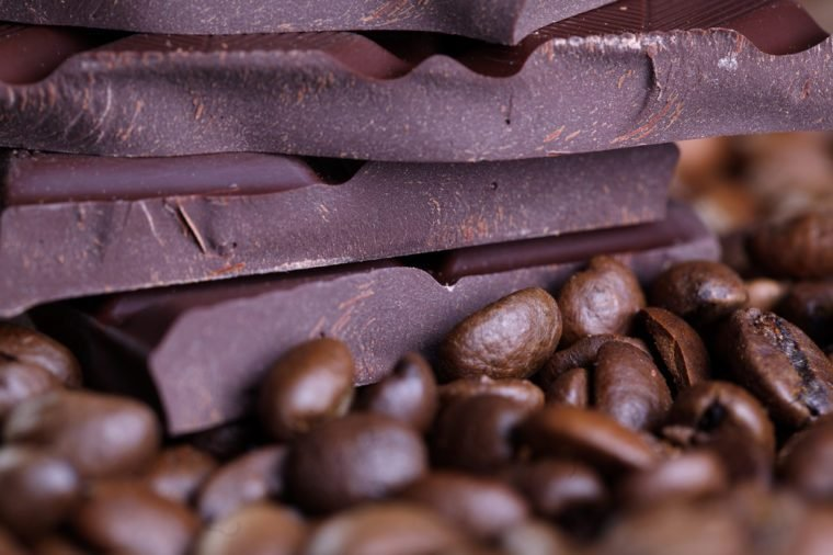 Fresh roasted coffee beans and stack of brown chocolate