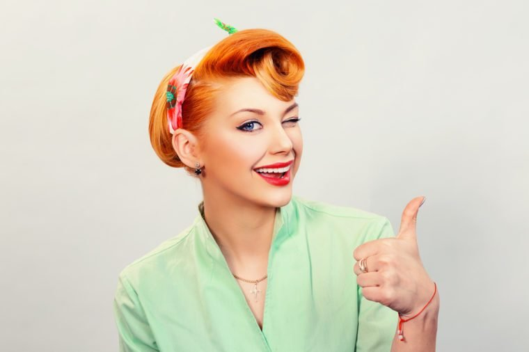 Closeup red head young woman pretty pinup girl green button shirt giving thumbs up sign gesture looking at you camera isolated white background retro vintage 50's style. Human emotions body language