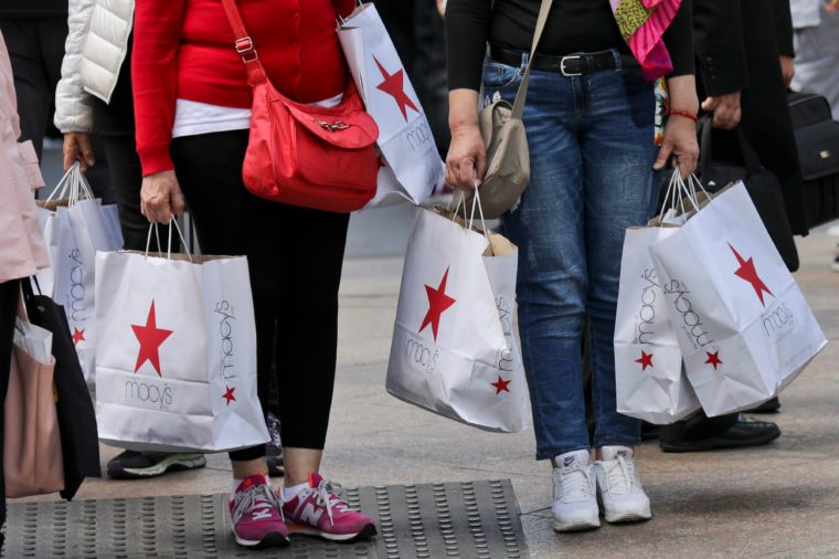 Shoppers holding bags from Macy's wait to cross an intersection in New York.
