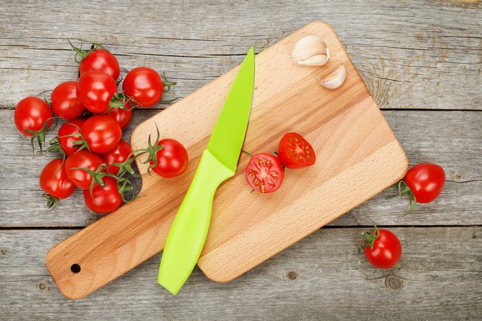 Cherry tomatoes with knife on cutting board over wooden table background