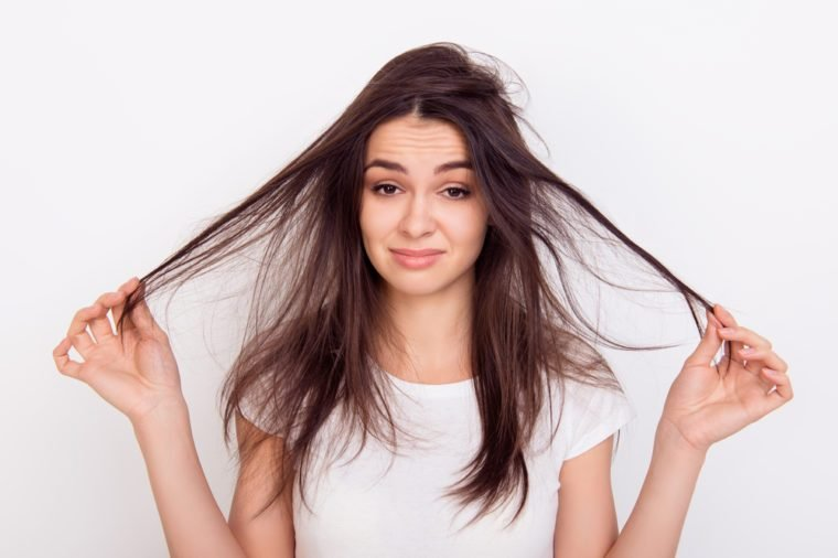 Sad girl showing her damaged hair while standing white background