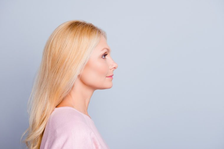 Half-face close up portrait of confident serious focused attractive stunning gorgeous mature lady with long smooth soft healthy hair looking aside isolated on gray background copy-space