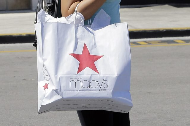A shopper carries a bag as she walks in the parking lot of a shopping mall.