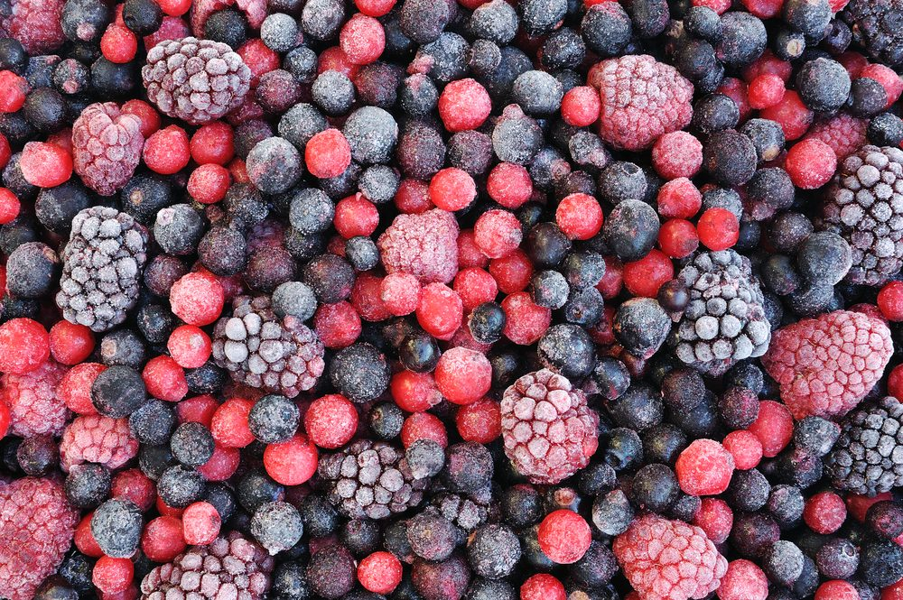 Close up of frozen mixed fruit - berries - red currant, cranberry, raspberry, blackberry, bilberry, blueberry, black currant