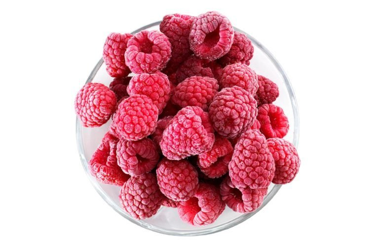 Frozen raspberries in a glass bowl - top view - isolated on white background