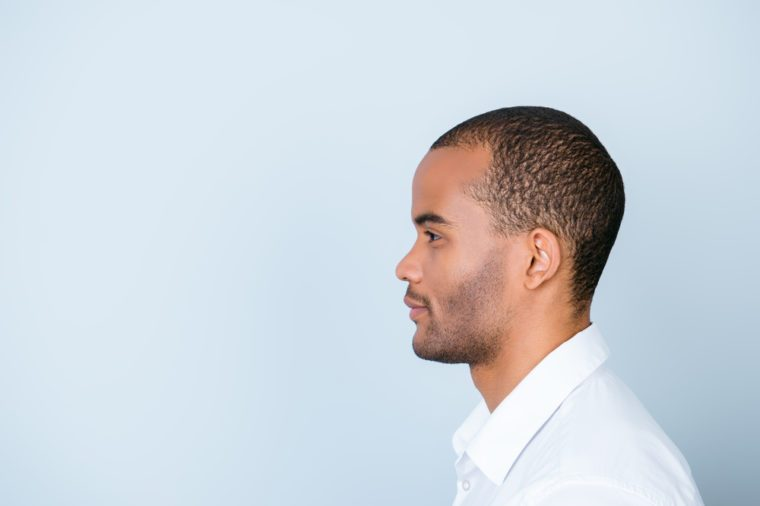 Profile side photo of mulatto american business guy standing in white formal outfit on pure blue background near the copy space