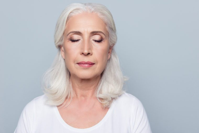 Close up portrait of confident concentrated mature woman with wrinkles on face, with closed eyes, with nude make up, isolated on gray background