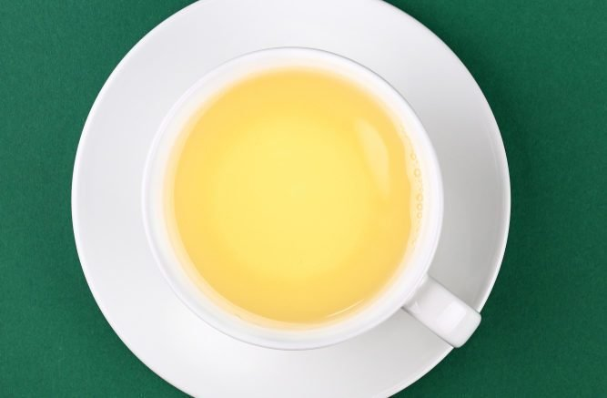 Close up one full white cup of green oolong tea on saucer on green table background, elevated top view, directly above
