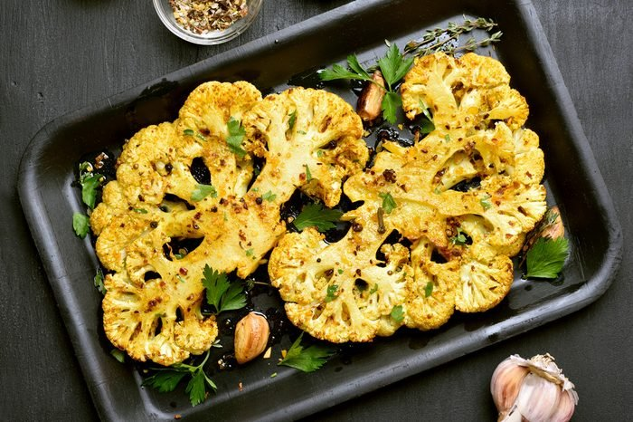 Baked cauliflower steaks with herbs and spices on baking sheet over black stone background.