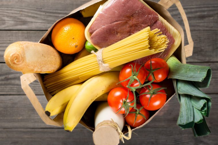 Full paper bag of various groceries on wooden background, top view