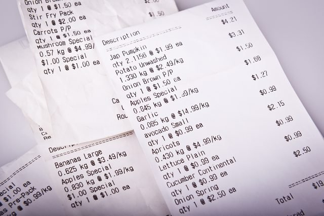 Pile of generic grocery receipts with costs shown in shallow focus