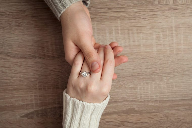 Top view of a male and female holding hands after a proposal of marriage. Female wearing an engagement ring