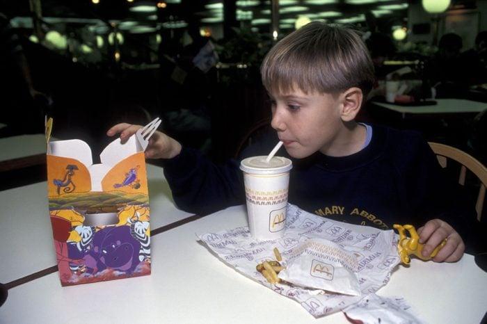 MODEL RELEASED Boy eating McDonalds happy meal UK