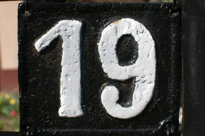 Old retro weathered cast iron plate with number 19 closeup