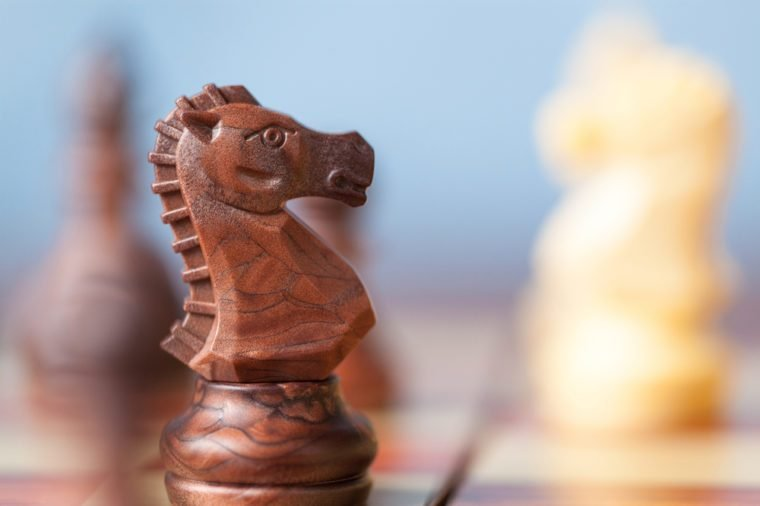 Black knight chess piece on the board with blue background.