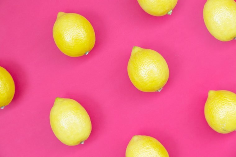 Top view of colorful fruit pattern of fresh lemon on pink background