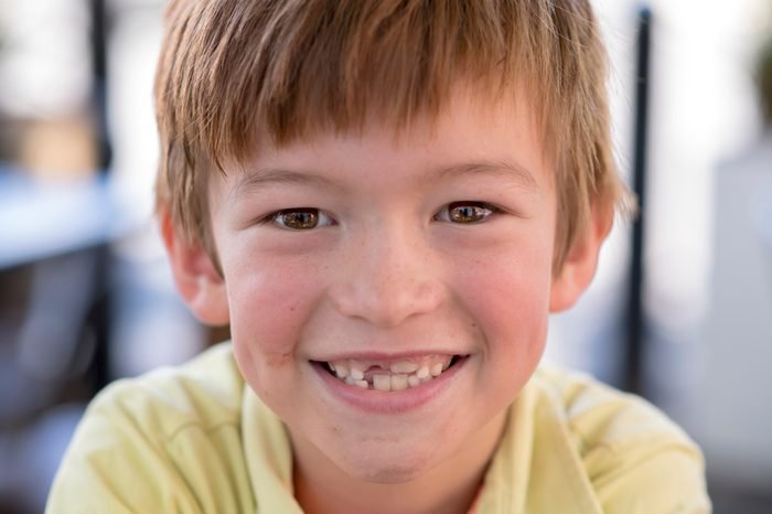 close up headshot portrait of young little 7 or 8 years old boy with sweet funny teeth smiling happy and cheerful in joy face expression looking at the camera in childhood lifestyle concept