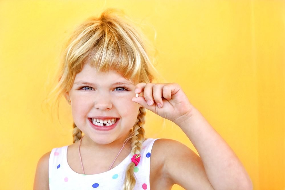 Smiling girl holding missing tooth