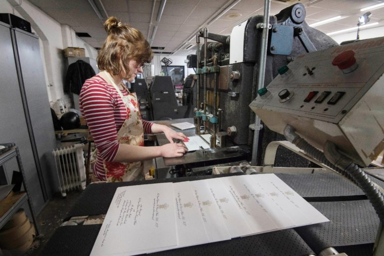 Lottie Small use the die stamping press at the workshop of Barnard and Westwood in London, who are printing the invitations for Prince Harry and Meghan Markle's wedding