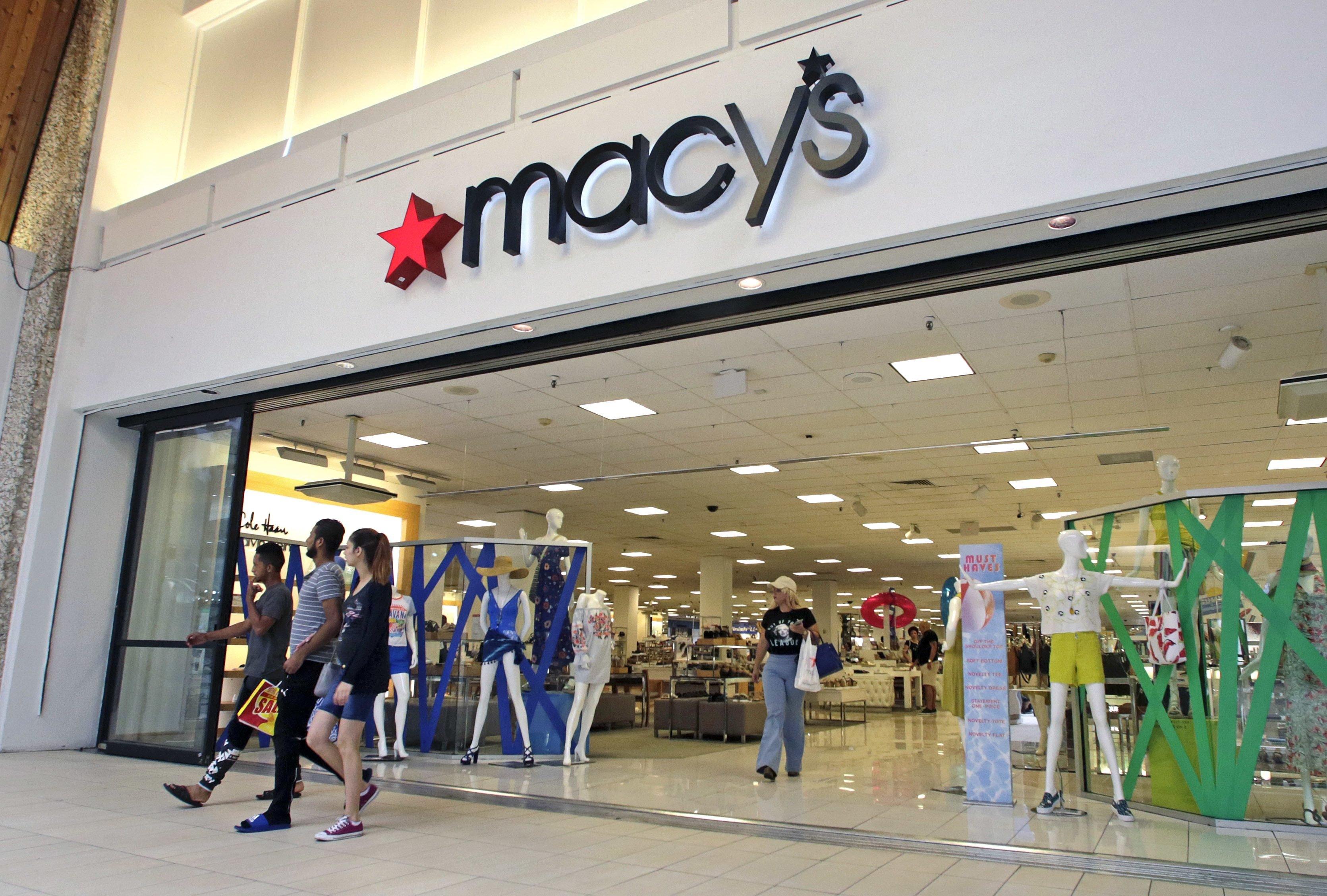 People walk out of a Macy's department store in Hialeah, Fla.