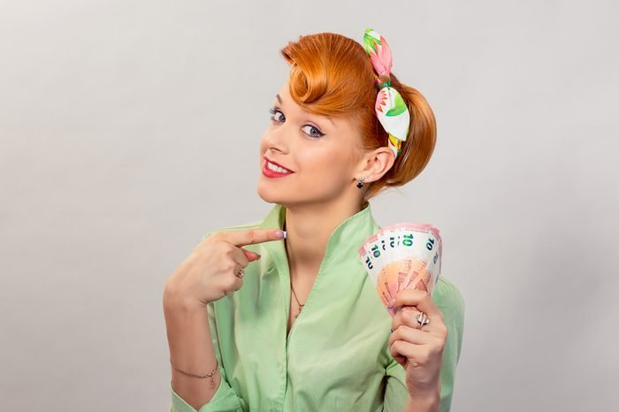 Money. Closeup portrait beautiful young pretty business woman fashion girl looking at you camera holding showing pointing money european currency isolated yellow background wall. Lottery win concept