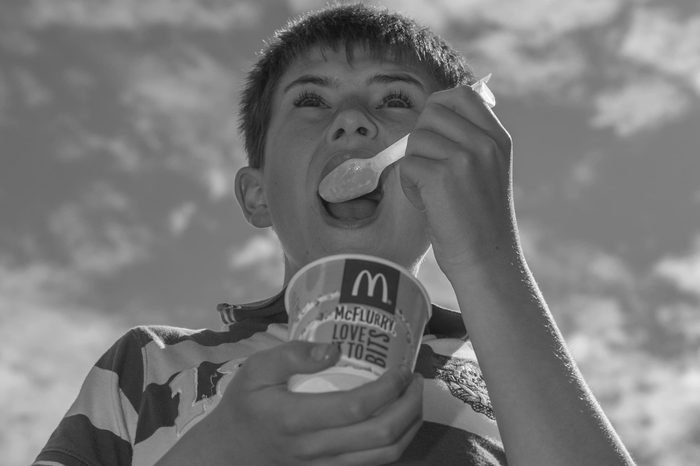 A 12 year old boy eating a mcdonalds Mcflurry ice cream outdoors in the uk