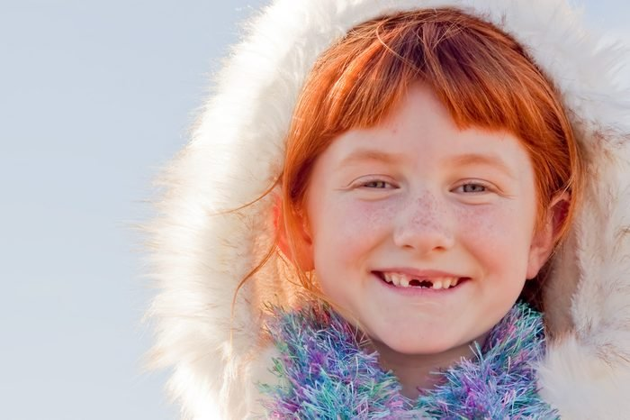 six year-old red haired girl with two front teeth missing and wearing Eskimo style fur lined hood