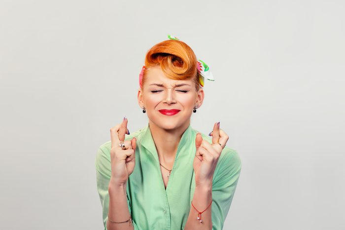 Closeup portrait of a smiling pin up retro vintage hair style woman with fingers crossed gesture isolated on a white grey background