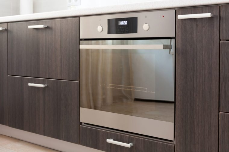 Kitchen cabinets with metal handles and built-in electric oven