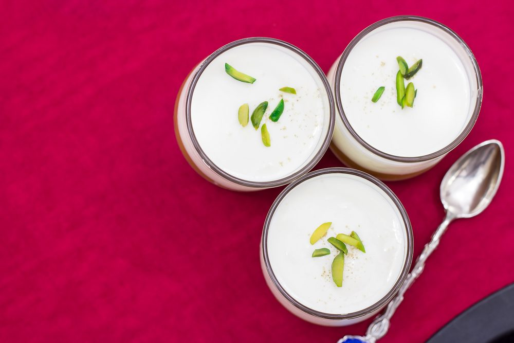 Three small jars of the panna cotta with pistachio on a red napkin. Top view, selective focus.