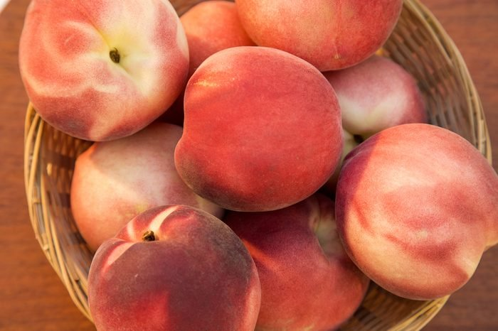 Some peaches in a basket over a wooden surface seen from above