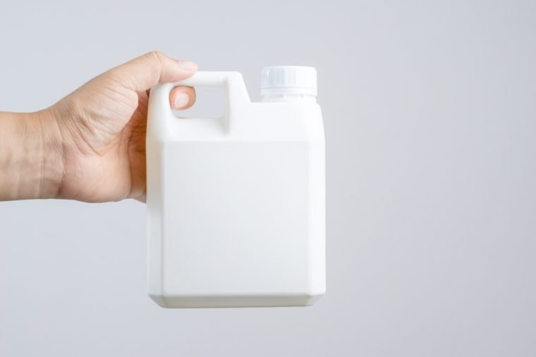 Hand holding 1000 cc, a liter plastic bottle or 0.26 gallon capacity for containing fertilizer or industrail liquid on white background